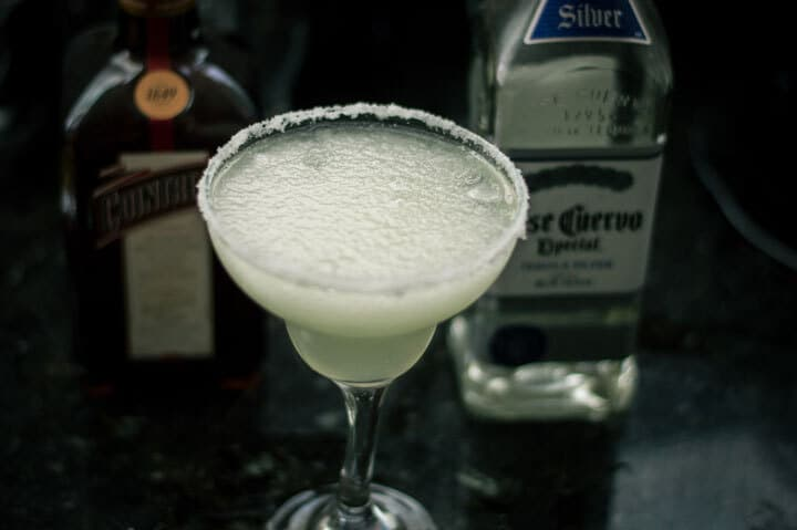 Frozen margarita drink with bottles of tequila and triple sec